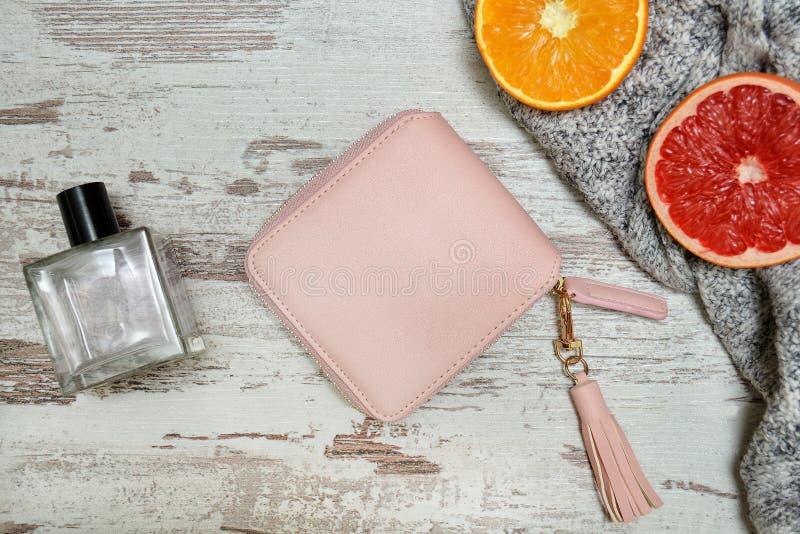 Wenig rosa weiblicher Geldbeutel, Parfüm und Zitrusfrucht auf einem hölzernen backgro stockfotografie
