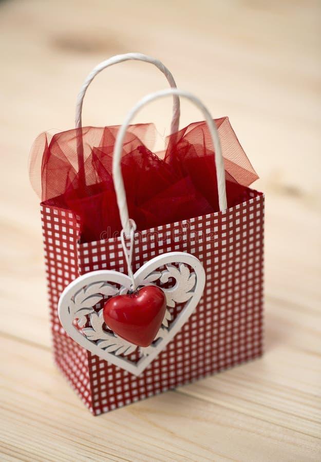 Wenig rote Tasche mit einem dekorativen Motiv eines Herzens auf hölzernem Hintergrund lizenzfreie stockfotos