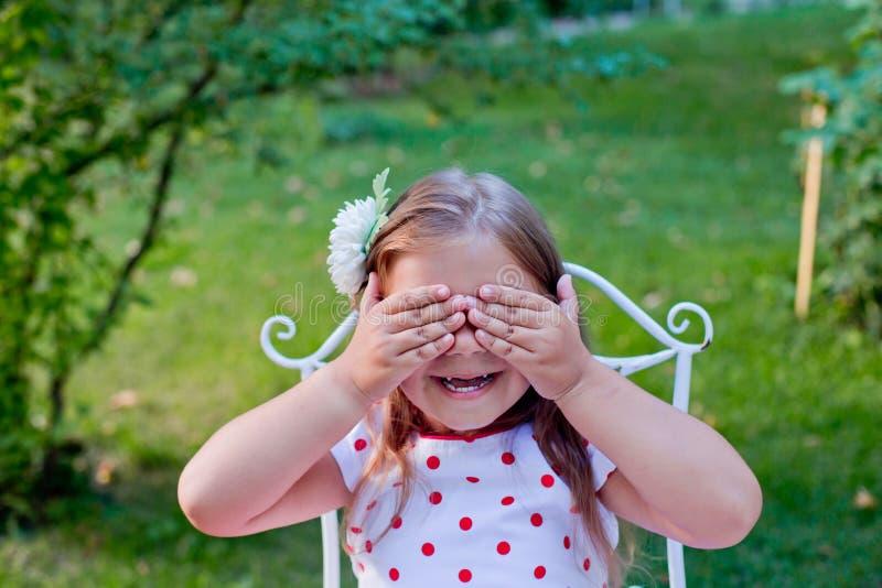 Wenig schönes Mädchen umfasste Augenhände stockfotografie