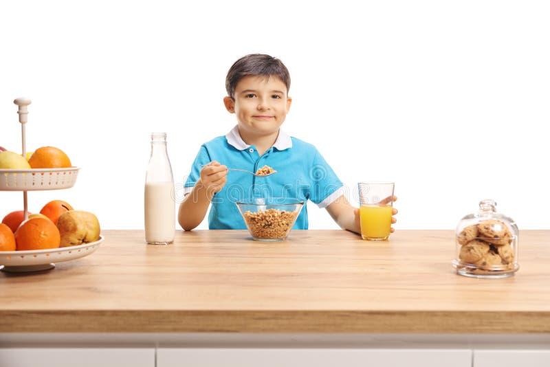 Wenig Schüler, der Getreide isst und Orangensaft an einem hölzernen Zähler trinkt stockfoto