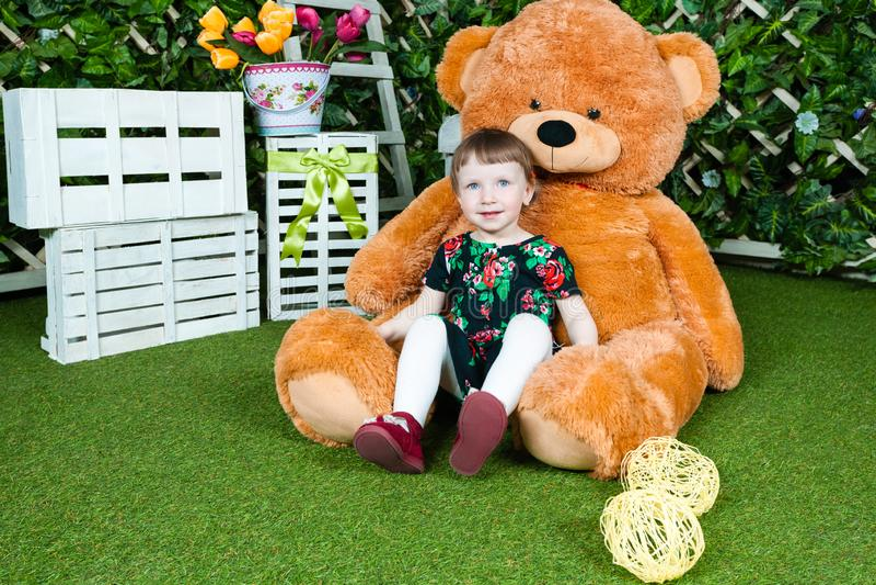 Wenig sch?nes M?dchen und ein enormer Teddyb?r Efeuwand im Hintergrund lizenzfreie stockbilder