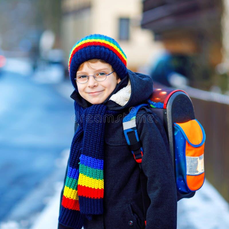 Wenig Schulkinderjunge der grundlegenden Klasse gehend zur Schule w?hrend der Schneef?lle Gl?ckliches gesundes Kind mit den Gl?se lizenzfreie stockbilder
