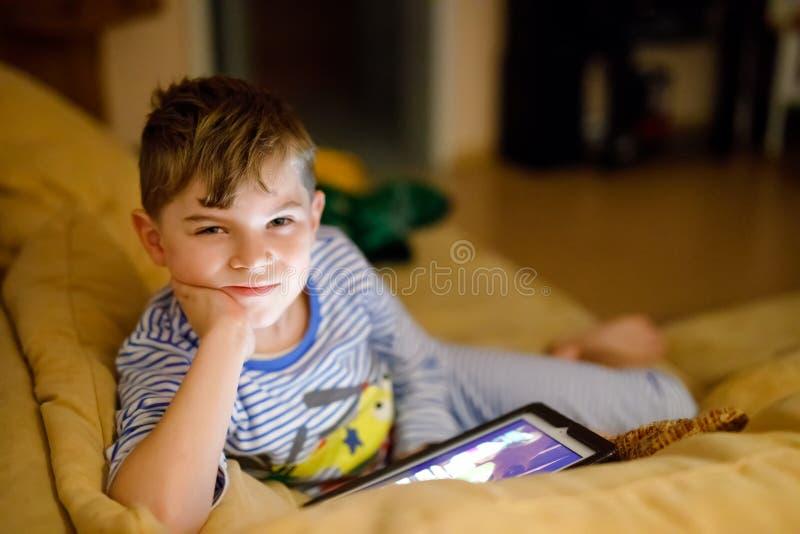 Wenig Schulkinderjunge, der Hausarbeit mit Tablette macht Schulkindlesung und Lernen mit dem Computer, suchend nach stockbilder