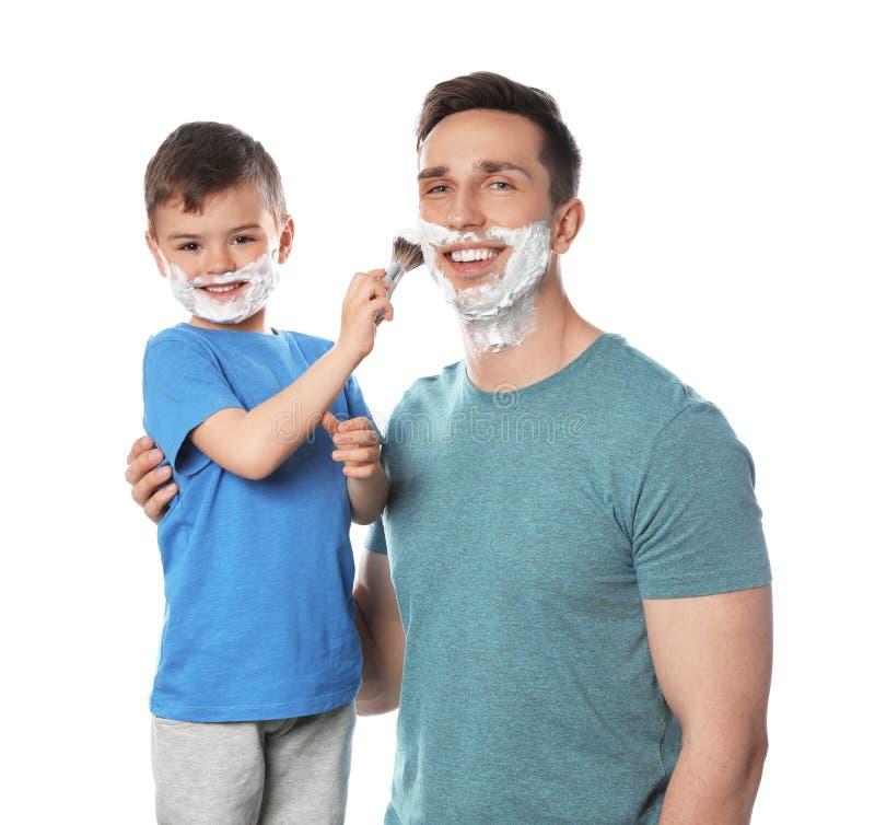 Wenig Sohn, der Schaum auf das Gesicht des Vatis gegen Wei? rasierend zutrifft stockbilder