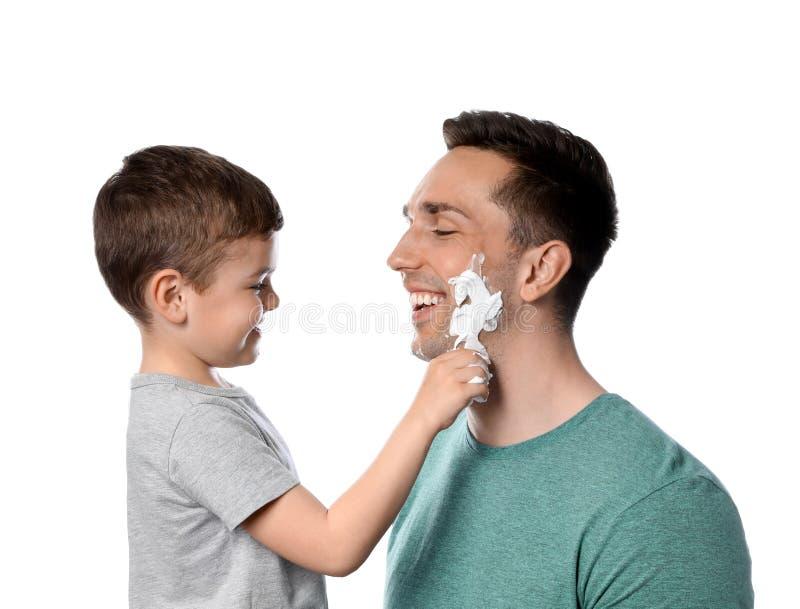 Wenig Sohn, der Schaum auf das Gesicht des Vatis rasierend zutrifft lizenzfreie stockbilder