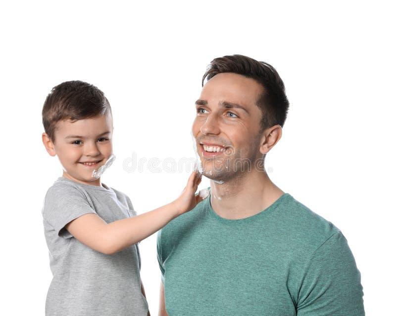 Wenig Sohn, der Schaum auf das Gesicht des Vatis rasierend zutrifft lizenzfreies stockbild