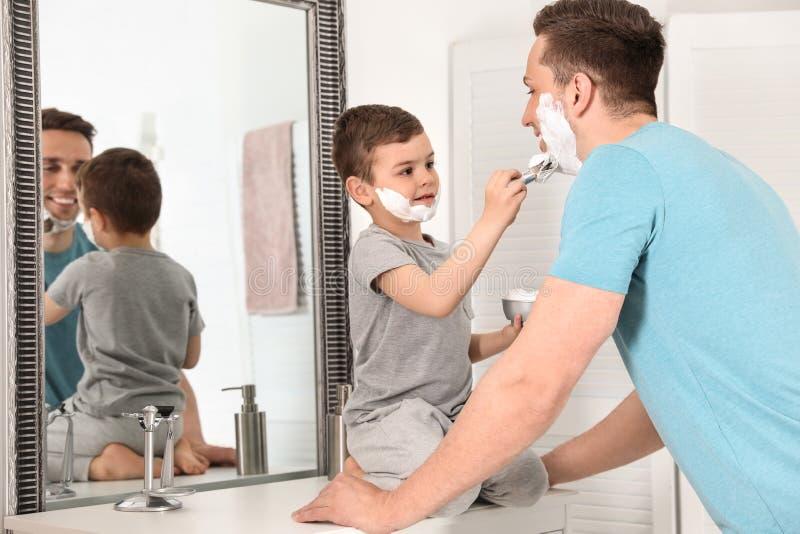 Wenig Sohn, der Schaum auf das Gesicht des Vatis rasierend zutrifft lizenzfreie stockfotografie