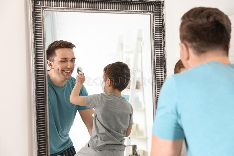 Wenig Sohn, der Schaum auf das Gesicht des Vatis rasierend zutrifft lizenzfreies stockfoto