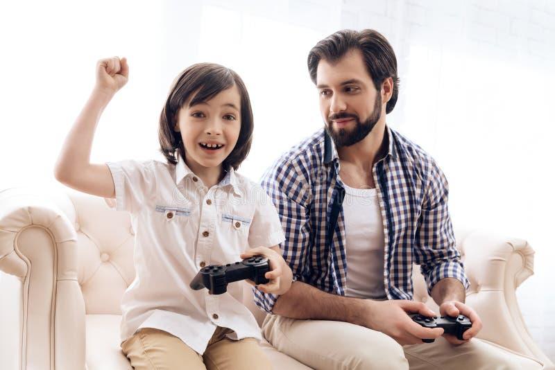 Wenig Sohn mit Steuerknüppel freuen sich am Sieg im Spiel mit Vater stockbilder