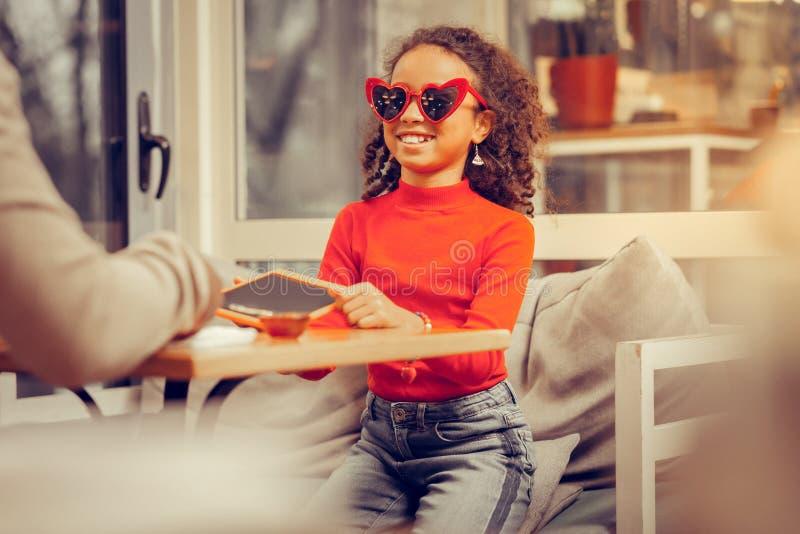 Wenig stilvolles Mädchen, das den roten Polohals trägt rote Herz-förmige Gläser trägt stockfoto