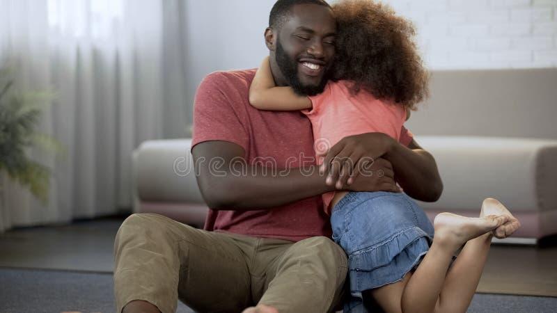 Wenig Tochter, die fest geliebten Vati, ausgezeichnetes Verhältnis in der Familie umarmt lizenzfreie stockfotos
