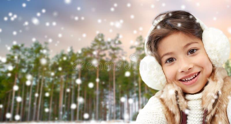 Wenig tragende Ohrenschützer des Mädchens über Winterwald lizenzfreies stockfoto