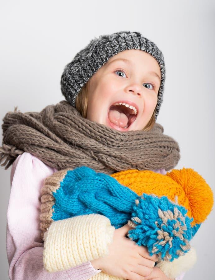 Wenig tragende Strickmütze, Schal und Strickjacke des Mädchens, einen Stapel von Hüten halten, lizenzfreie stockbilder