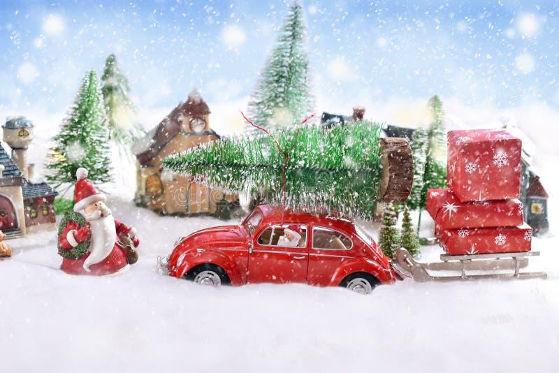 Wenig tragender Weihnachtsbaum des roten Autos des Spielzeugs auf die Oberseite stockfoto