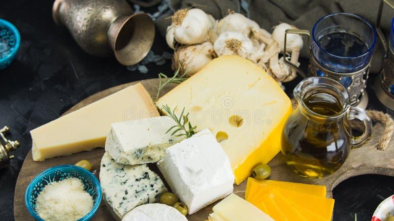 Wenig unterschiedliche Art von Käsen mit Oliven Papier und Olivenöl auf schwarzer Tafel in der Küche stockfoto