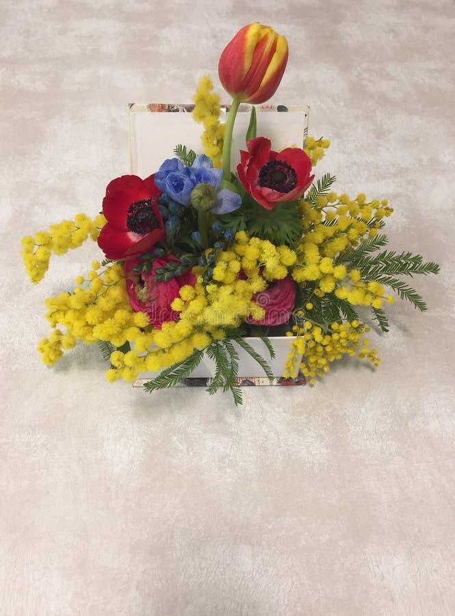 Wenig Vase mit Blumen Mimose, Tulpen, Veilchen und Mohnblumen auf einer Tabelle lizenzfreie stockfotografie