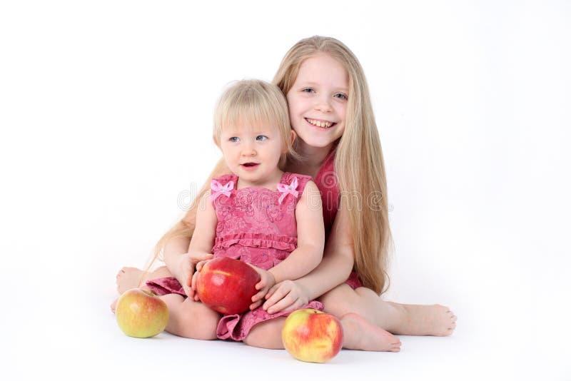 Wenig zwei Schwestern 9-jährig und einjährig mit Apfel O lizenzfreie stockbilder