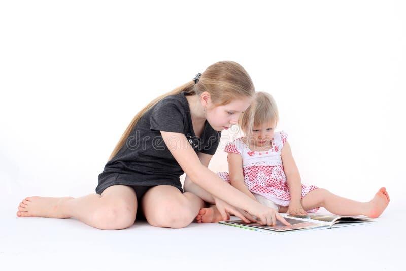 Wenig zwei Schwestern 9-jährig und einjähriges gelesenes Buch stockfoto