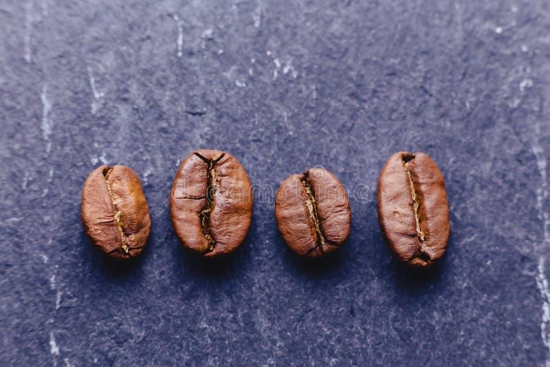 wenige Kaffeebohnen auf schwarzem Stein lizenzfreie stockfotografie