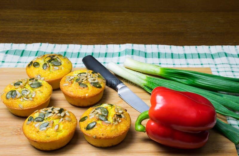 Wenige Muffins machten vom Maismehl mit Kürbis und Sonnenblumensamen und roter Pfeffer, Frühlingszwiebel und Messer auf hölzernem stockfoto