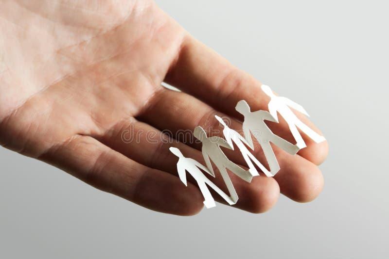 Wenige Papierausschnitleute an Hand lizenzfreie stockfotos