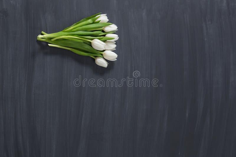 Wenige Tulpenblumen auf dunkler chalcboard Oberfläche Blumenstrauß auf einem Unschärfezusammenfassungshintergrund mit Kopienraum lizenzfreie stockfotografie