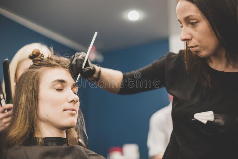 Wenkbrauw het verven De meester schildert wenkbrauwen met henna aan een mooi meisje, schildert met een borstel in de salon van ee royalty-vrije stock afbeeldingen