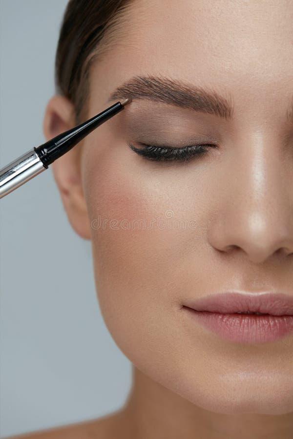 Wenkbrauwmake-up Schoonheidsmodel die brows met browpotlood vormen stock fotografie