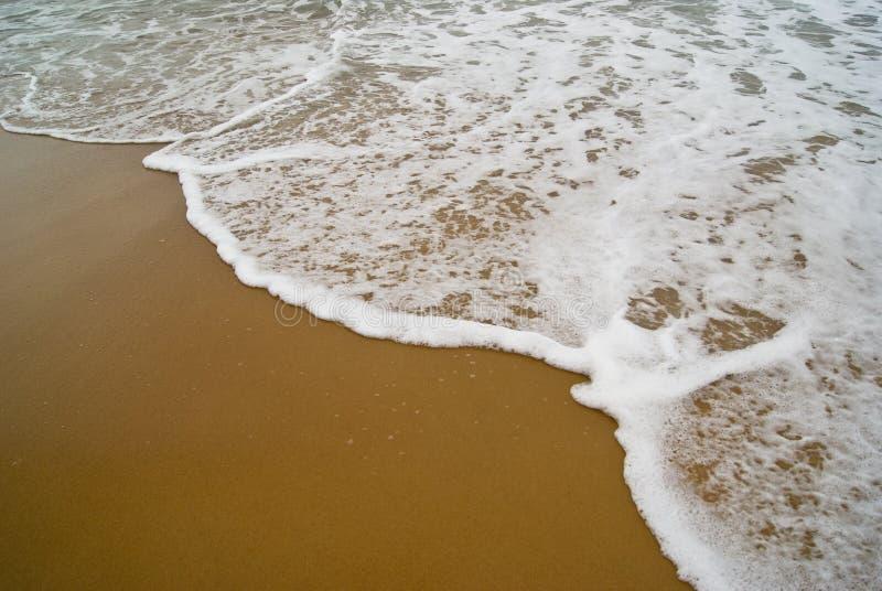 Wenn die Welle den Sand trifft stockbild