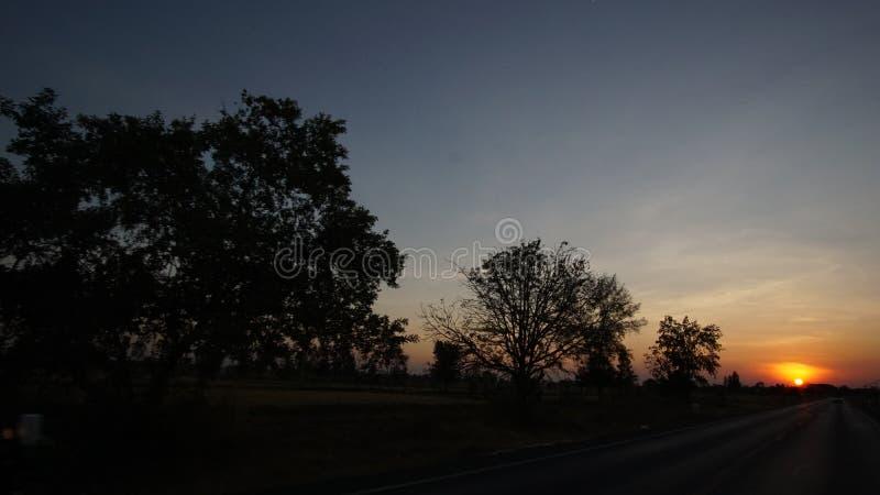 Wenn Sonnenuntergang an der Landstraße stockbilder