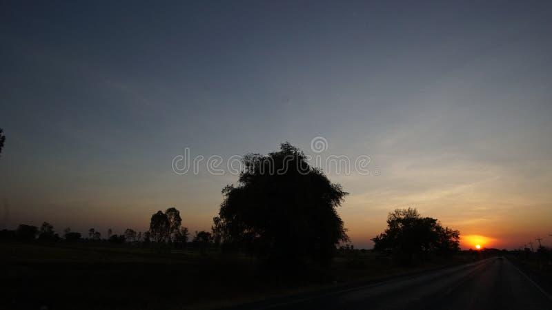 Wenn Sonnenuntergang an der Landstraße lizenzfreies stockfoto