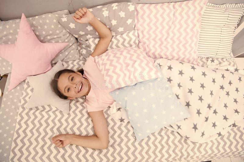 Wens haar goedemorgen Het meisjeskind legt op bed haar slaapkamer Jong geitje wakker en volledig van energie De prettige tijd ont stock foto's