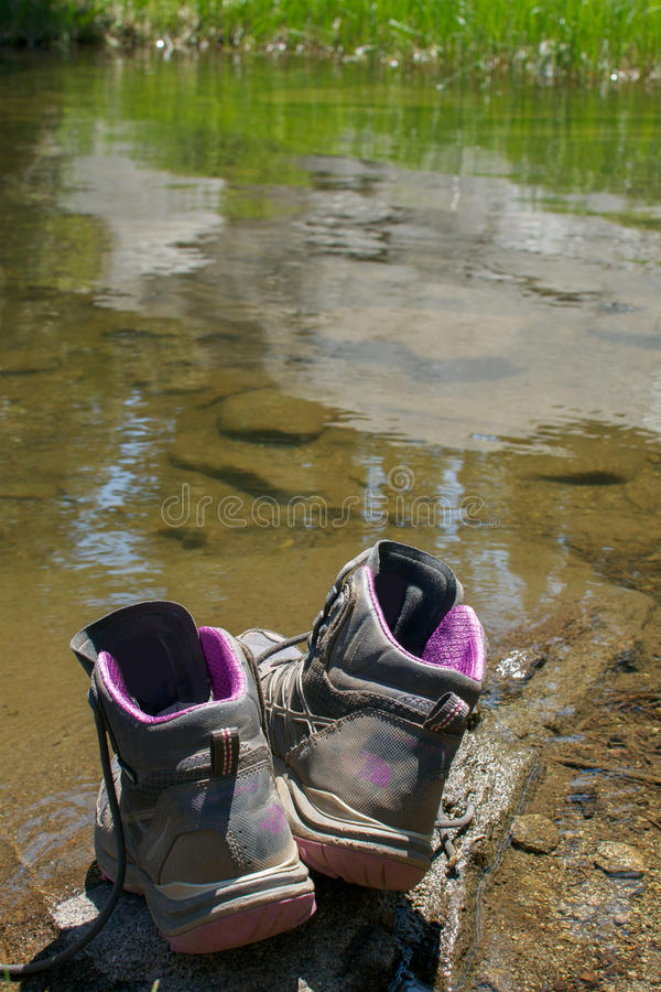 Went for a swimm. Pair of old, dusty hiking boots on a rock at the margin of a lake, suggesting that its owner is taking a swim - adventure in the outdoors stock photography