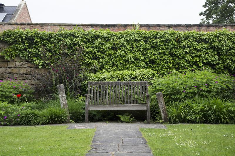 WENTWORTH, UK - June 1, 2018. Wooden bench in gardens set within the grounds of Wentworth Woodhouse. Rotherham, South Yorkshire,. Wooden bench in gardens set royalty free stock photo