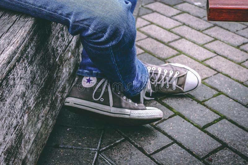 Wer auf der Bench sitzt, trägt braune konverse All-Star-Sneakers und Blue Denim Jeans stockfotografie