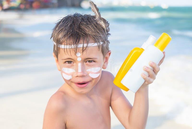 Wer sind ich? Lichtschutzsonnenschutzmittel ist auf Hippie-Jungengesicht, bevor es während der Sommerferien auf Strand sich bräun lizenzfreie stockfotografie