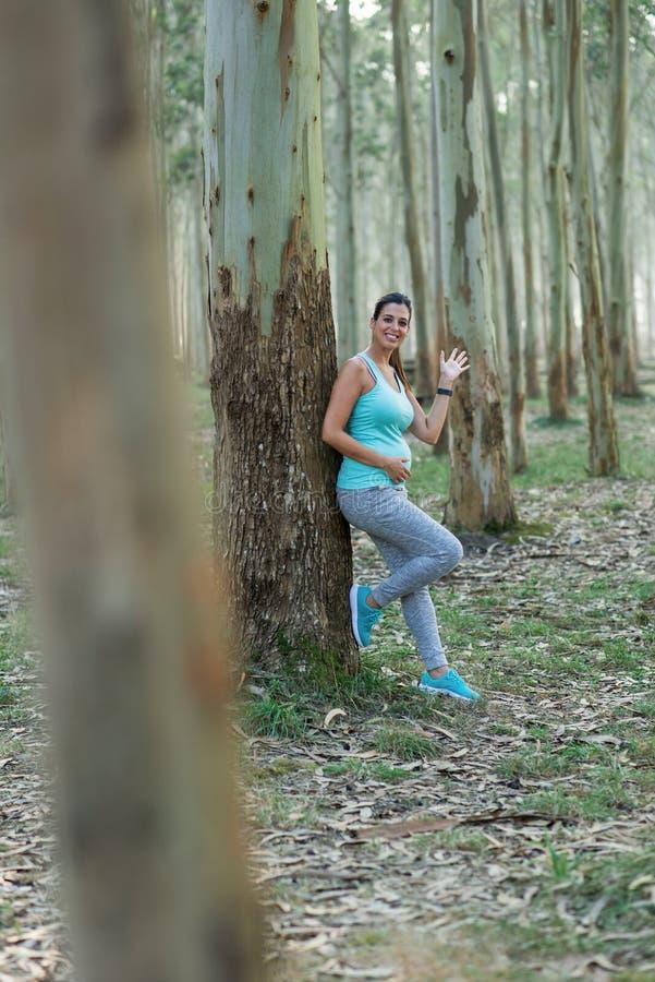 Werdende Mutter der gesunden Eignung, die einen Trainingsrest und -c$wellenartig bewegen nimmt stockbild