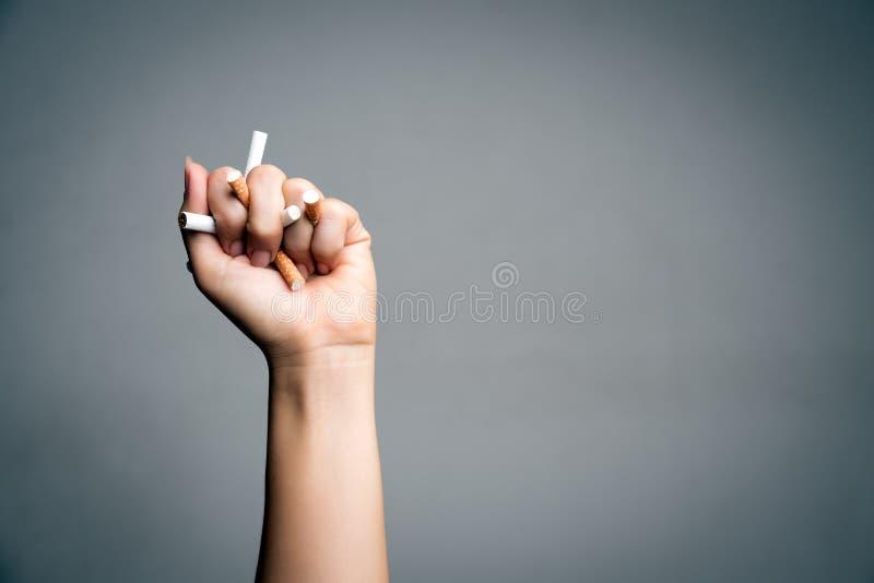Wereld Geen Tabaksdag, 31 Mei Het roken van het einde Sluit omhoog Mensenhand die en sigaretten op grijze achtergrond verplettere royalty-vrije stock foto's