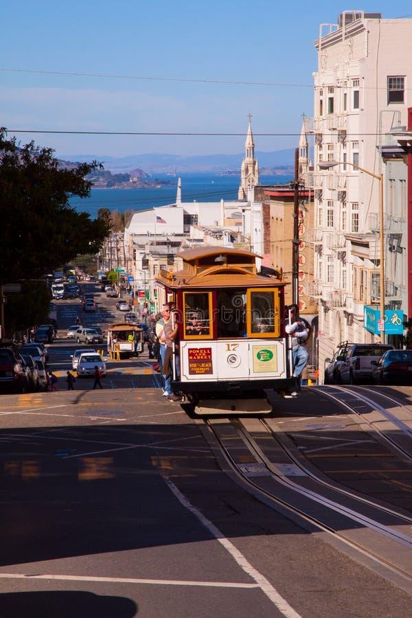 Wereldberoemde Kabelwagen in een straat van San Francisco, de V.S., met blauwe hemel en overzees op de achtergrond stock foto's