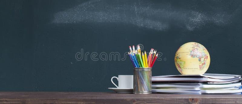 Wereldbol op notitieboekjes op het bureau van de schoolleraar royalty-vrije stock afbeeldingen