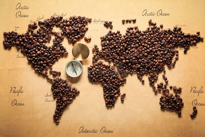 Wereldkaart van geroosterde koffiebonen wordt gemaakt met kompas, hoogste mening die stock foto
