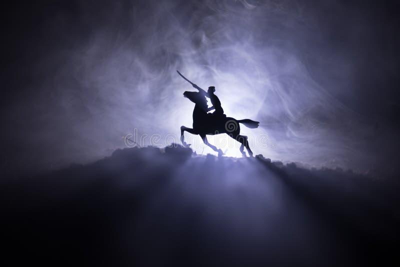 Wereldoorlogambtenaar (of strijders) ruiter op paard met een zwaard klaar te vechten en militairen op een donkere mistige gestemd royalty-vrije stock afbeelding