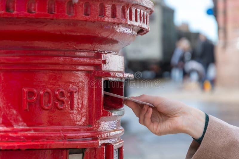 Werfen eines Buchstaben in einem roten britischen Briefkasten lizenzfreie stockbilder