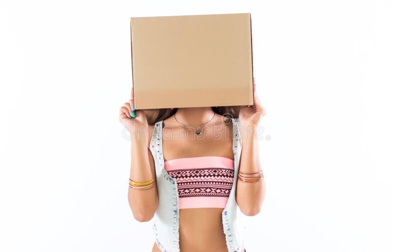 Werfen Sie das anonyme Mädchen, das mit ihrem Gesicht steht, das unter einer Pappschachtel versteckt wird, tragende jugendlich Au lizenzfreie stockbilder
