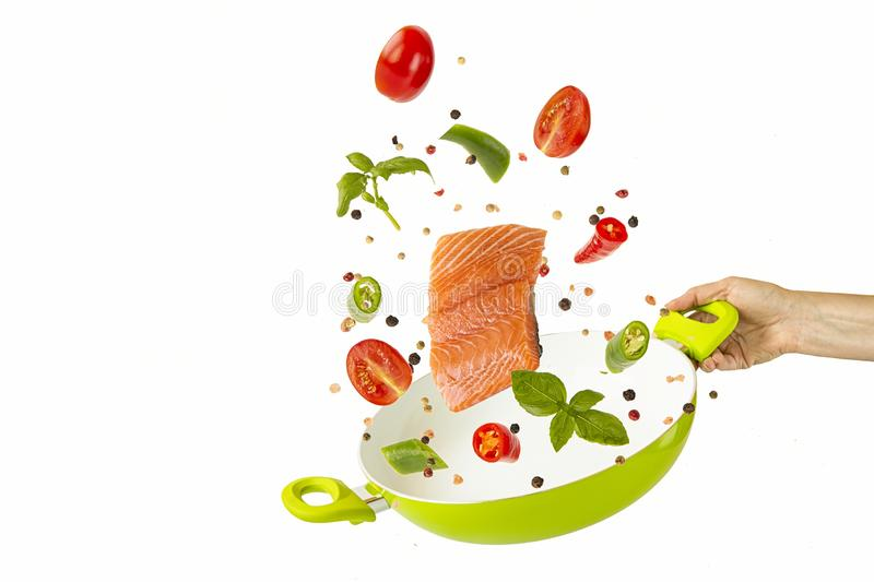 Throw the fish and vegetables with spices into the green frying pan. objects on white background. Flying Food. Throw the fish and vegetables with spices into the royalty free stock photos