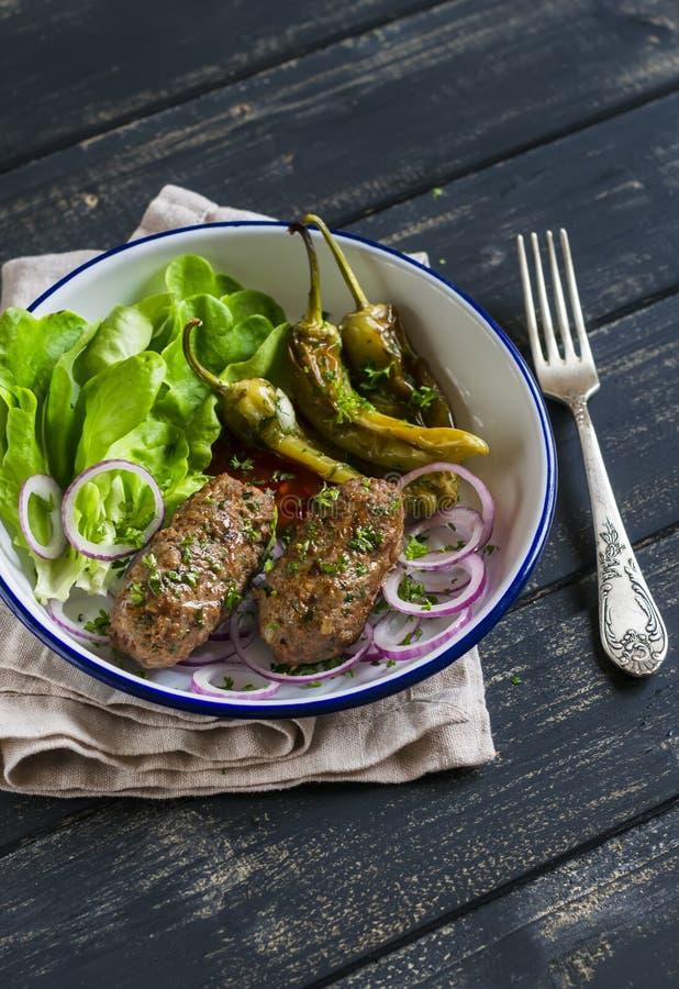 Werfen Sie Kebab, würzige gebratene Pfeffer und frischen grünen Salat auf der Platte auf einer dunklen Holzoberfläche stockfotografie