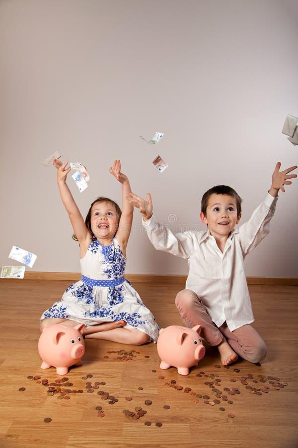 Werfende Banknoten des Mädchens und des Jungen stockbild