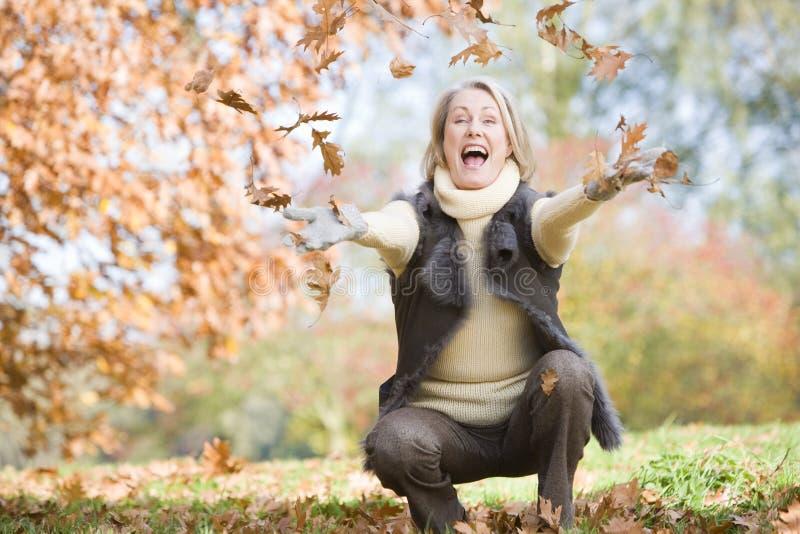 Werfende Blätter der älteren Frau in der Luft stockfoto