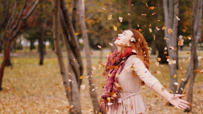 Werfende Blätter der glücklichen Frau in einem Herbst Frohe und aufgeregte junge Frau, die Spaß im Fallpark hat stockbilder