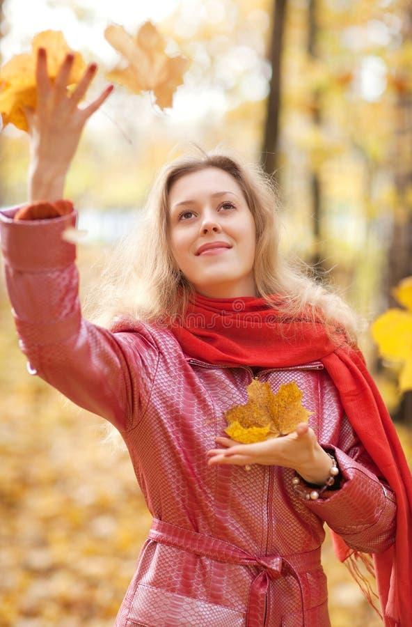 Werfende Blätter der jungen Frau lizenzfreie stockbilder